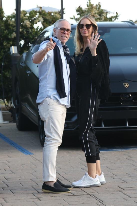 Томми Хилфигер в голубой рубашке и белых джинсах