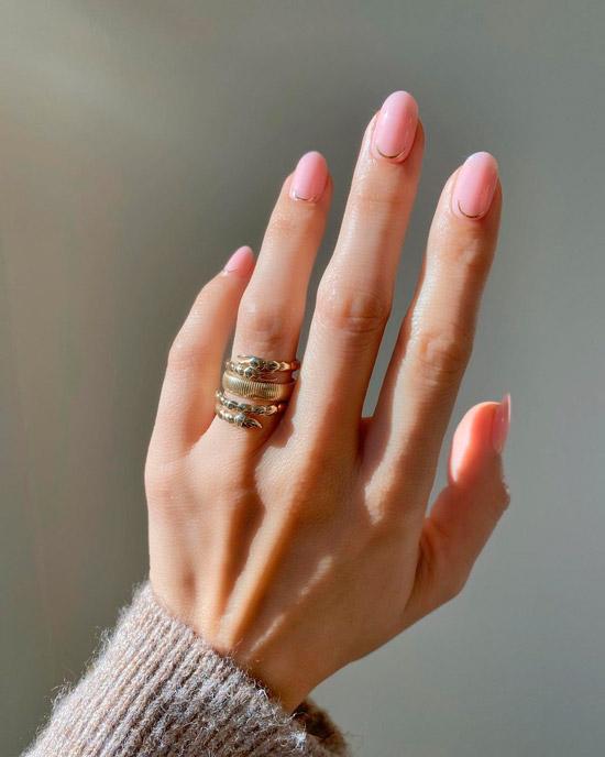 Нежный розовый маникюр с золотой полосой на овальных ногтях средней длины