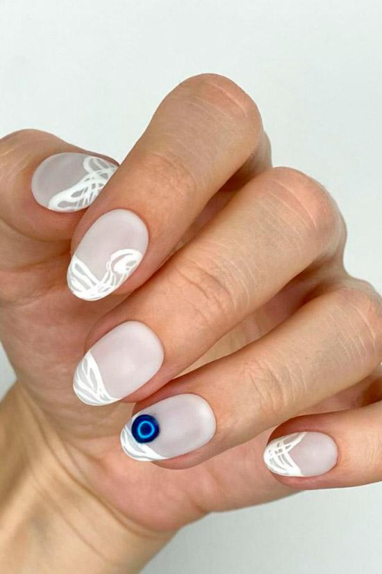 классный белый маникюр с узорами на коротких овальных ногтях