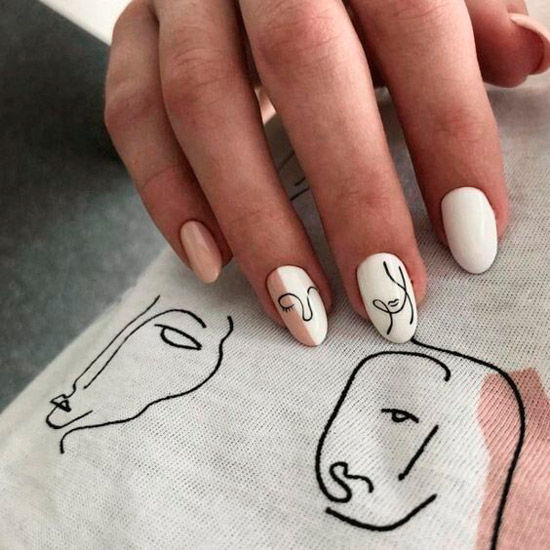 Белый маникюр с черными узорами на овальных ногтях