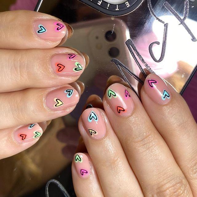 Бежевый маникюр с разноцветными сердечками на коротких овальных ногтях