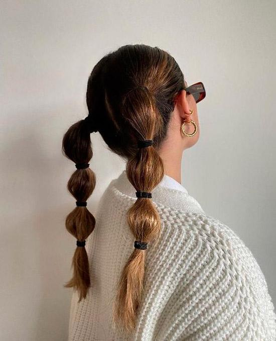 Девушка с двумя хвостиками с резинками на темных волосах средней длины