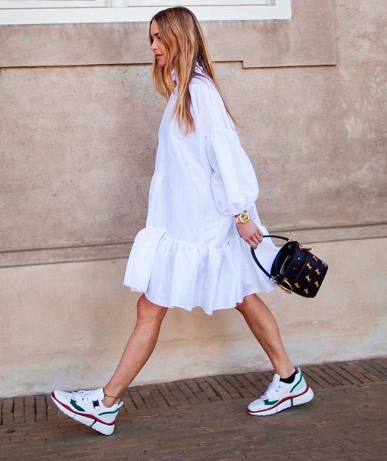 Девушка в белом просторном платье, белые кроссовки с цветными вставками