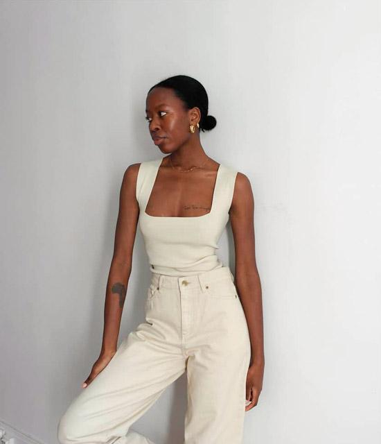 Девушка в белом топе с квадратным вырезом и светлые джинсы
