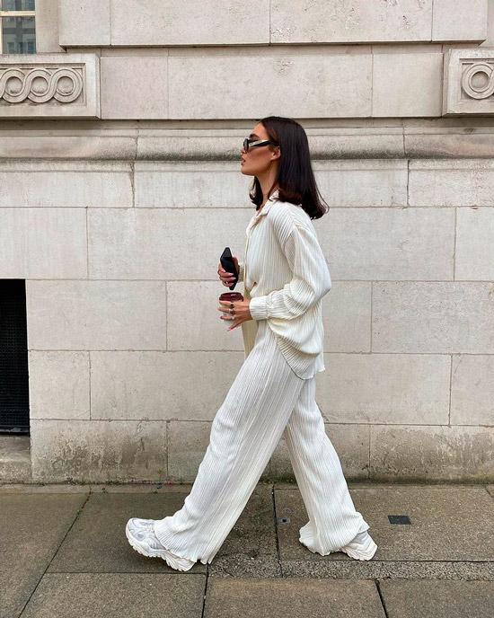 Девушка в белых просторных брюках, блузка оверсайз и белые кроссовки