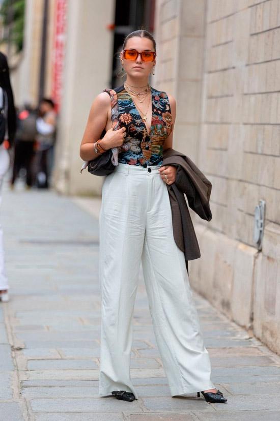 Девушка в белых свободных брюках, черный топ с принтом и туфли на каблуке, образ дополняют солнцезащитные очки и сумочка