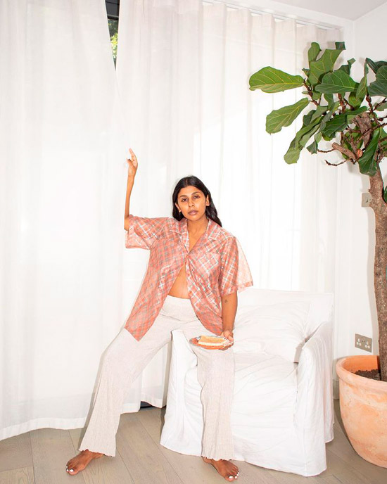 Девушка в белых свободных брюках и розовой рубашке оверсайз