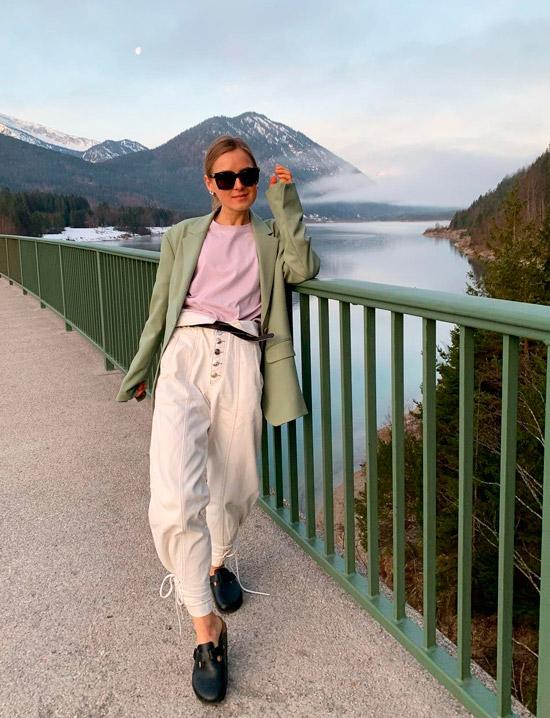 Девушка в бежевых брюках с ремнем, пиджак оверсайз и футболка пастельного оттенка, черные лоферы и солнцезащитные очки завершают образ