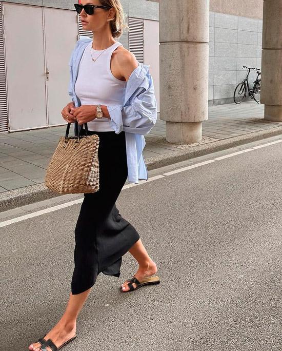Девушка в черной узкой юбке, белая майка, рубашка оверсайз, образ завершают простые сланцы и соломенная сумка