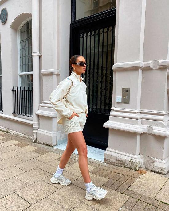 Девушка в мини шортах, бежевая олимпийка и объемные белые кроссовки