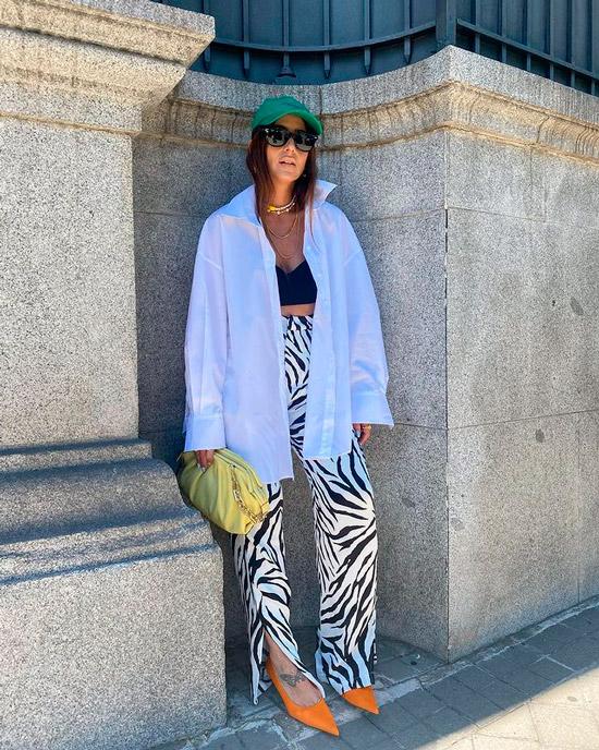Девушка в модных брюках с принтом зебры, черный топ бюстье и рубашка оверсайз, образ дополняют оранжевые туфли и кепка