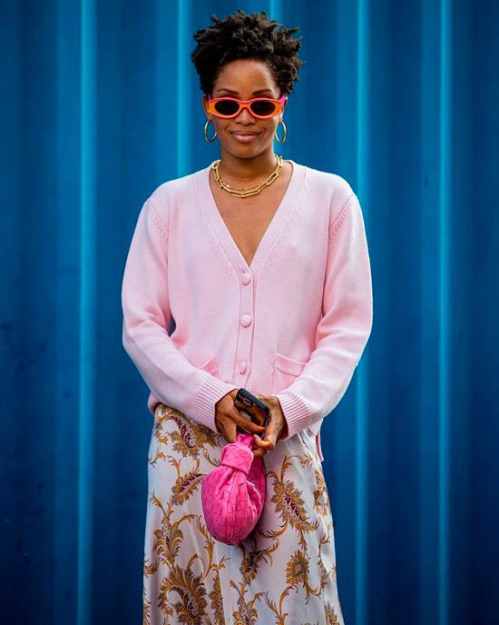 Девушка в нежно розовом кардигане, белая шелковая юбка с принтом, яркая розовая сумочка и солнцезащитные очки