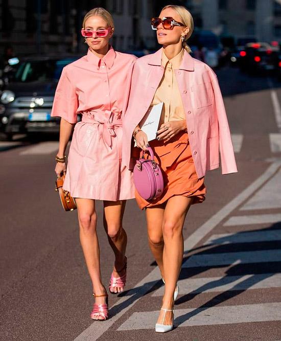 Девушка в нежно розовой мини юбке, рубашка и босоножки на ремешках, образ дополняют розовые солнцезащитные очки и сумочка
