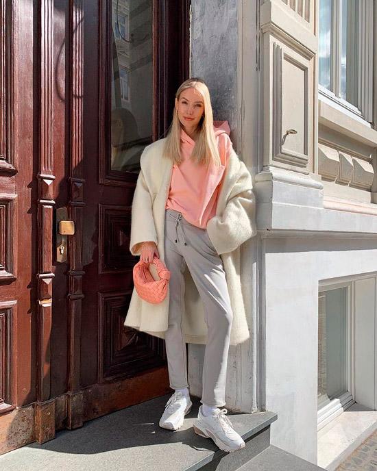 Девушка в серых спортивных брюках, розовое худи и белое пальто, образ дополняют белые кроссовки и мини сумочка