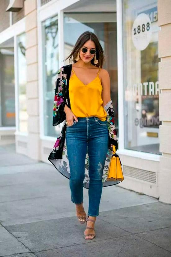 Девушка в синих джинсах с завышенной талией, желтый топ и черное кимоно с цветочным принтом