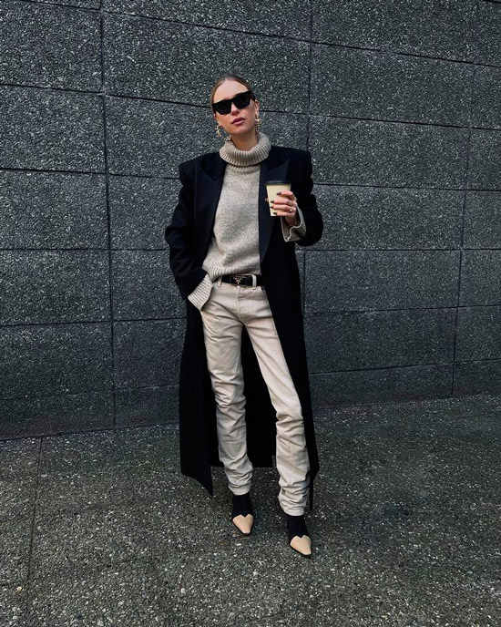 Девушка в светлых джинсах, черный ремень, свитер и черное длинное пальто