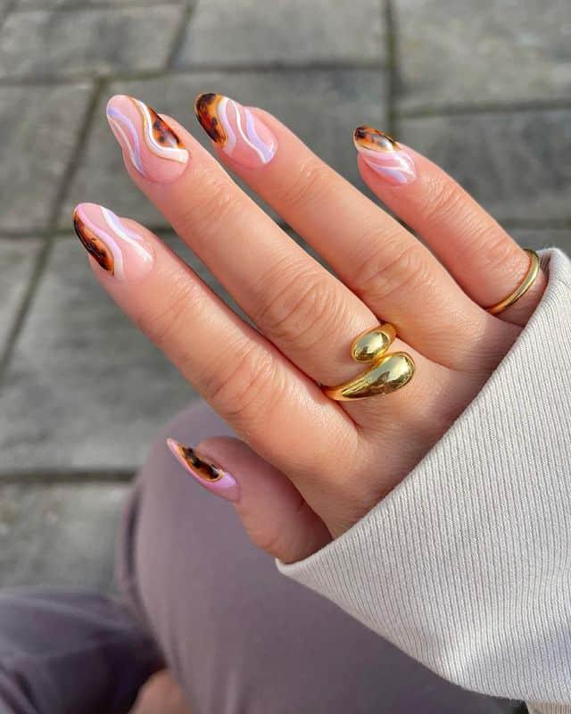 Интересный маникюр с черепашьим принтом и светлыми завитками на овальных ногтях