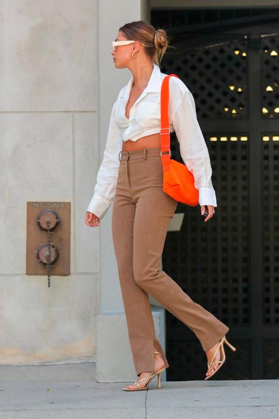 Модель в бежевых джинсах клеш, укороченная белая рубашка и туфли на ремешках