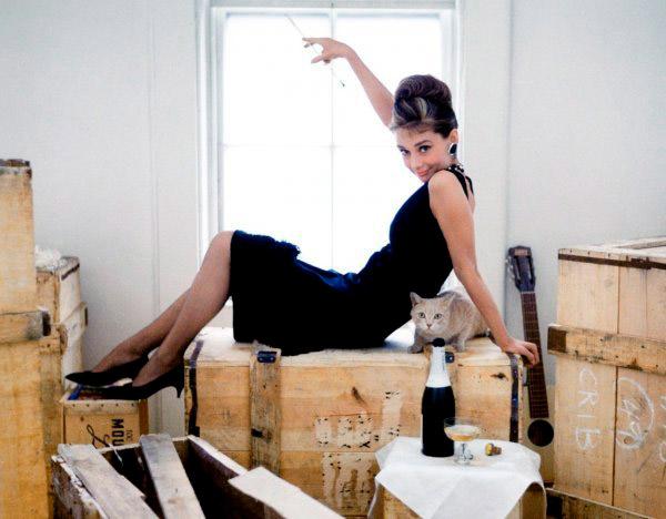 Одри Хепбёрн в черном платье футляр без рукавов, образ дополняют туфли на низком каблуке и украшения