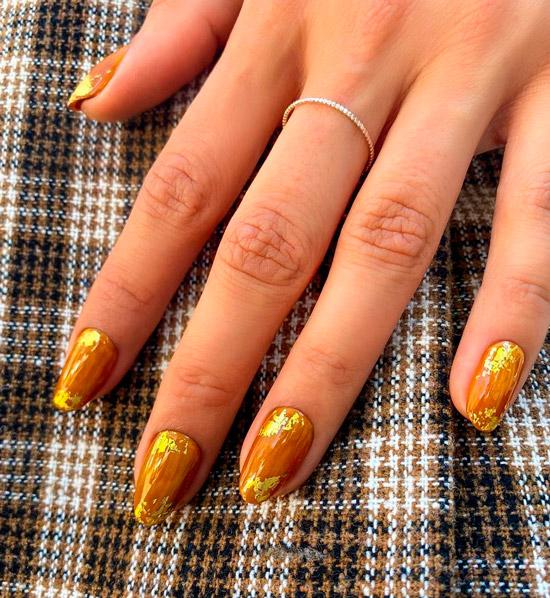 Оранжевый маникюр с золотыми хлопьями на овальных ногтях средней длины