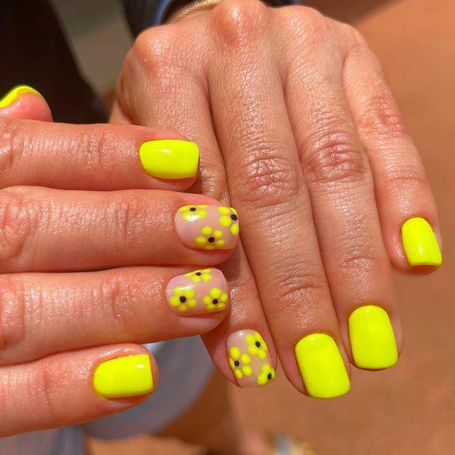 Желтый неоновый маникюр с цветочным принтом на коротких ногтях