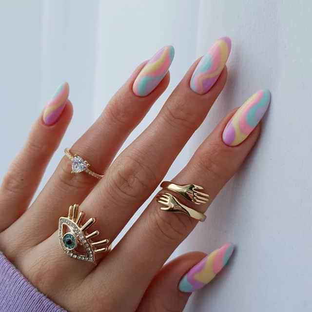красивый пастельный маникюр завитками на длинных овальных ногтях