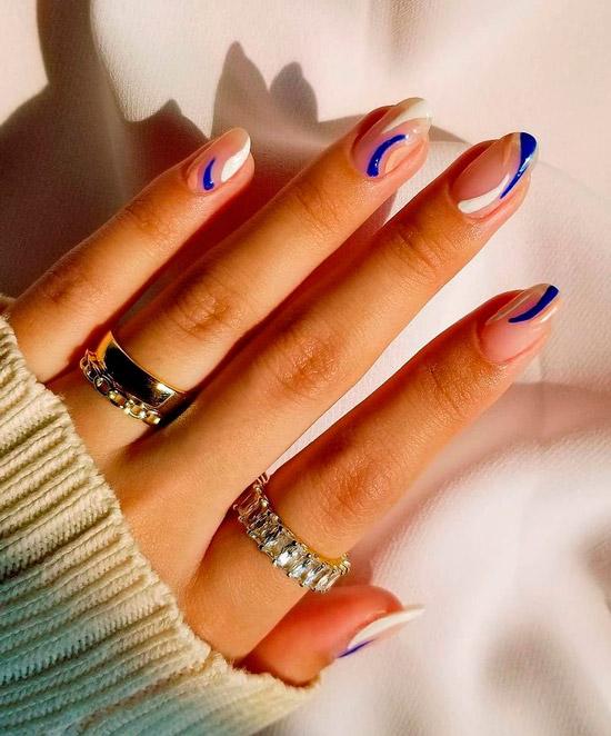 Абстрактный маникюр с белыми и синими линиями на овальных ногтях