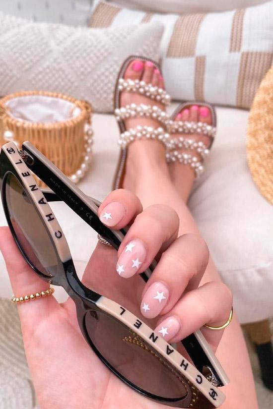 Бежевый маникюр с белыми звездами на овальных ногтях