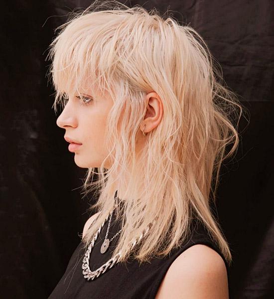 Девушка с многослойной стрижкой с челкой на светлых волосах средней длины