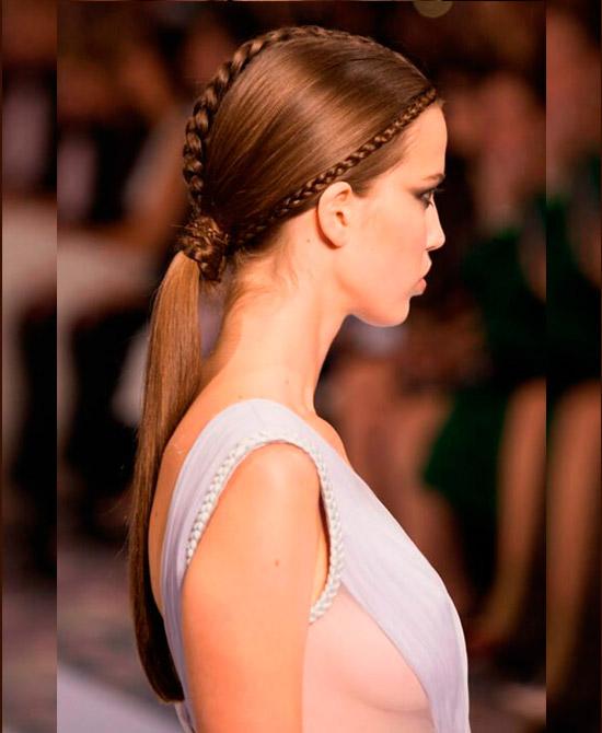 Девушка с низким гладким хвостом с тонкими косичками на медных волосах