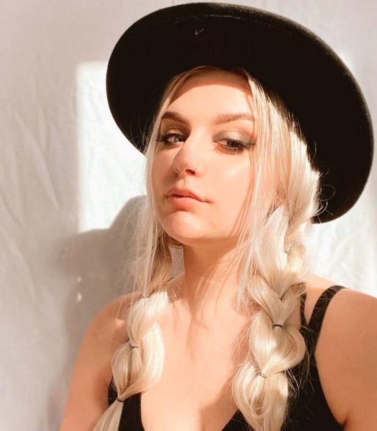 Девушка с воздушными косичками на светлых длинных волосах