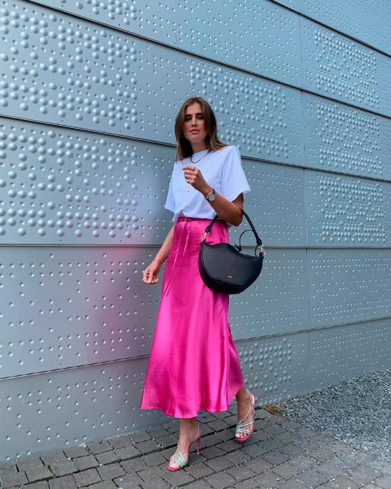 Девушка в атласной длинной юбке, простая белая футболка, образ дополняют босоножки на ремешках и черная сумка