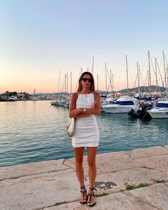 Девушка в белом мини платье, образ завершают солнцезащитные очки и простые сандалии