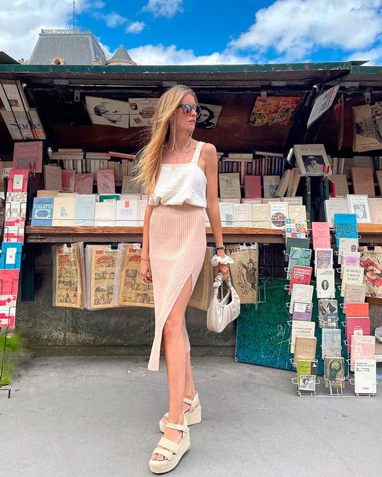 Девушка в белом топе на толстых бретельках, прямой розовой юбке с разрезом сбоку