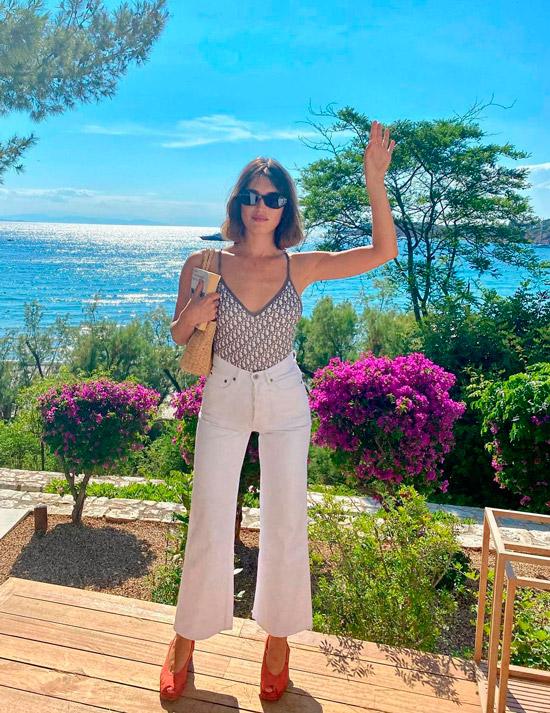 Девушка в белых укороченных джинсах, топ и оранжевые туфли с открытыми пальцами