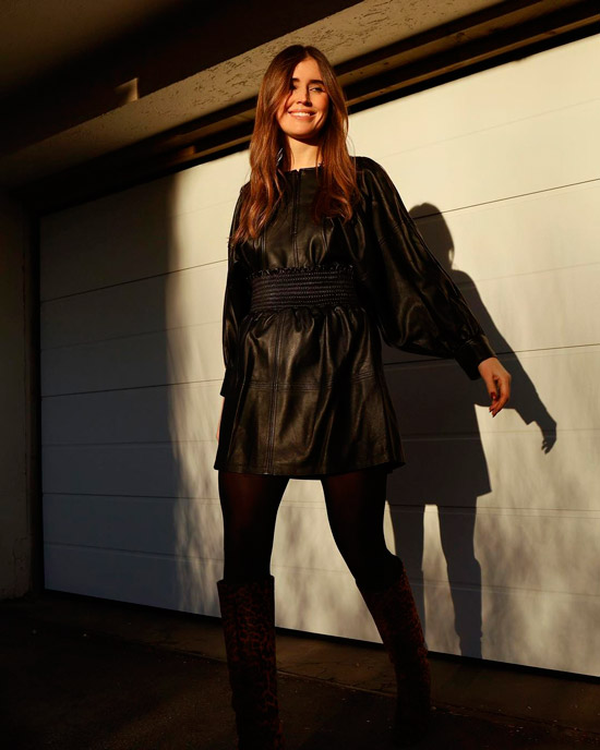 Девушка в черном кожаном платье с длинными рукавами