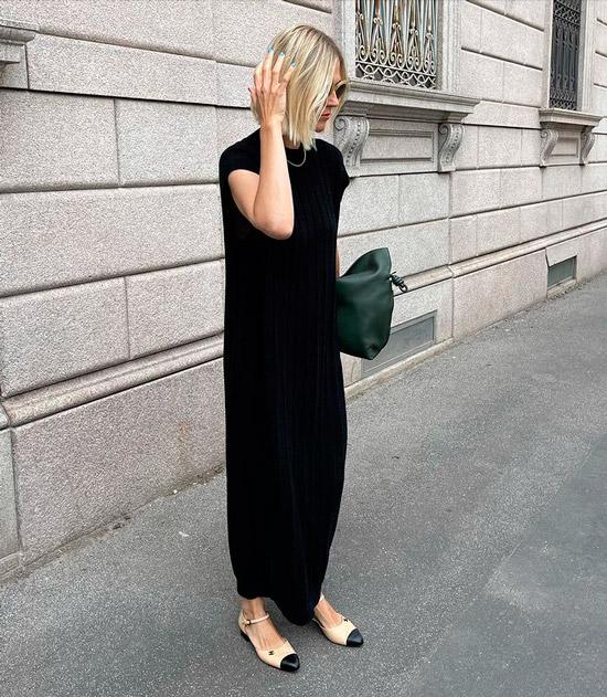 Девушка в черном трикотажном платье, бежевые балетки и мягкая сумка дополняют стиль