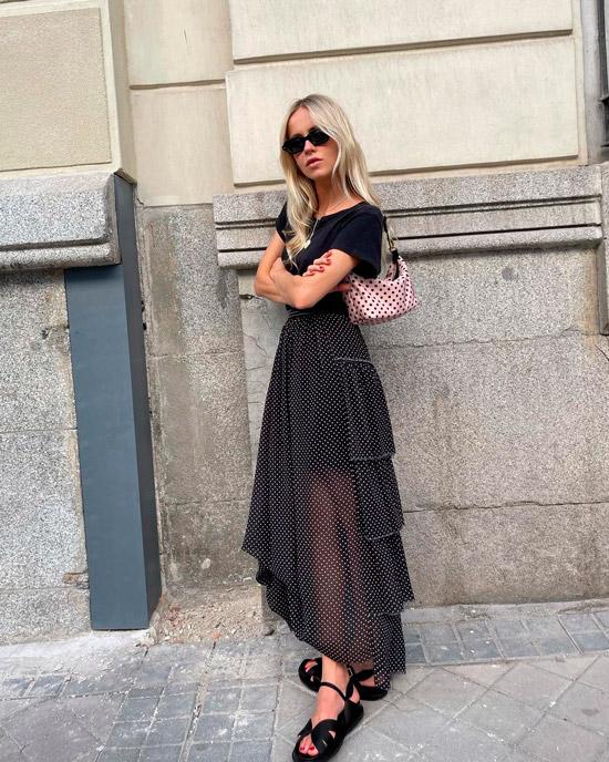 Девушка в черной юбке миди в белый горох, черной футболке и сандалиях