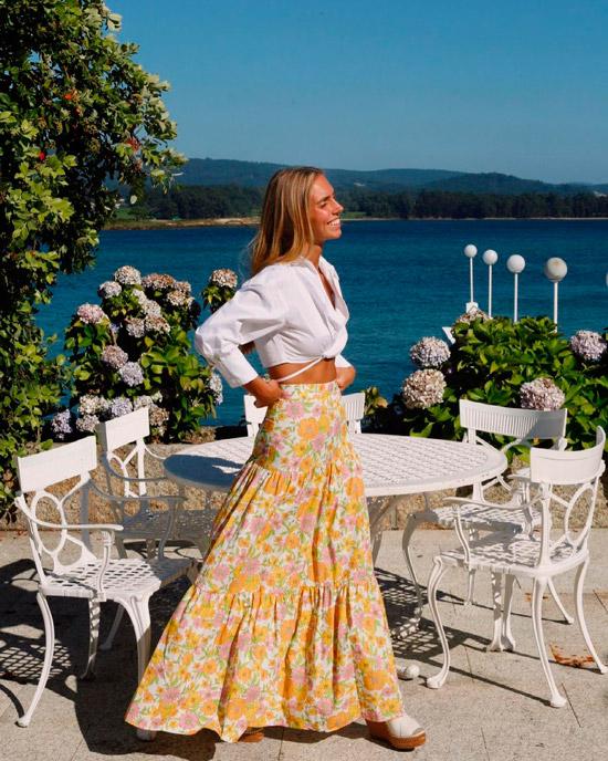 Девушка в длинной воздушной юбке с цветочным принтом, белая укороченная рубашка и босоножки