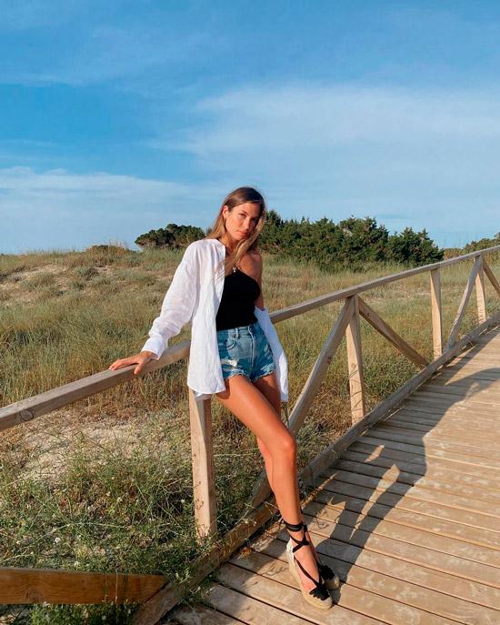 Девушка в джинсовых мини шортах, черный топ и рубашка оверсайз