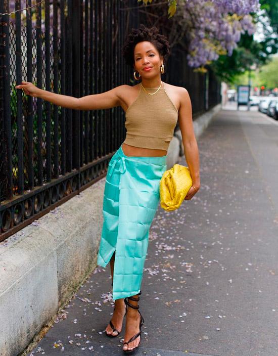 Девушка в голубой атласной юбке миди, бежевый топ, образ дополняют черные босоножки и мягкая сумочка