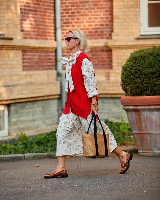 Девушка в легком платье миди с бантом, лоферы со змеинным принтом, красная жилетка дополняет образ