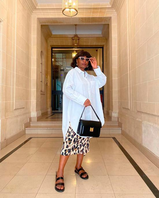 Девушка в леопардовой юбке миди, белая рубашка оверсайз, черные сандалии и сумочка