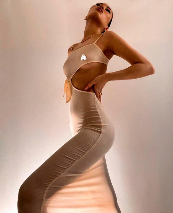Девушка в облегающем бежевом платье с вырезом