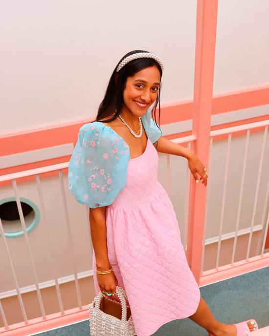 Девушка в простом розовом платье с воздушными пышными рукавами, образ завершает жемчужная сумочка и бусы