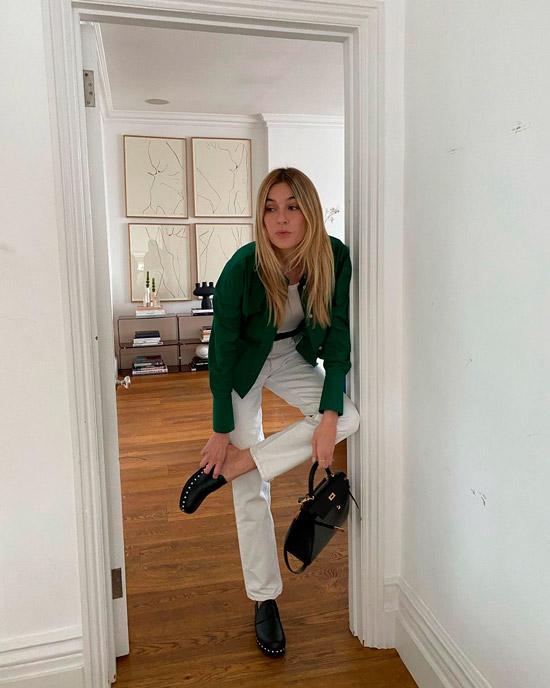 Девушка в прямых белых джинсах с ремнем и зеленом бомбере