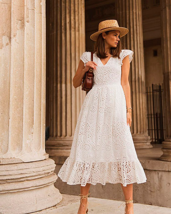 Девушка в романтическом белом платье миди с короткими рукавами, образ дополняет соломенная шляпа и коричневая сумочка