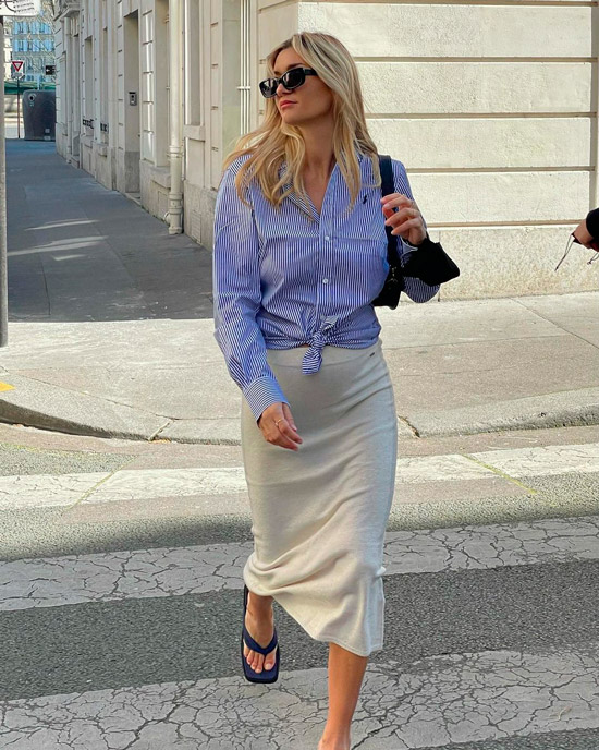 Девушка в светлой узкой юбке и голубой рубашке в полоску, образ дополняют солнцезащитные очки и босоножки