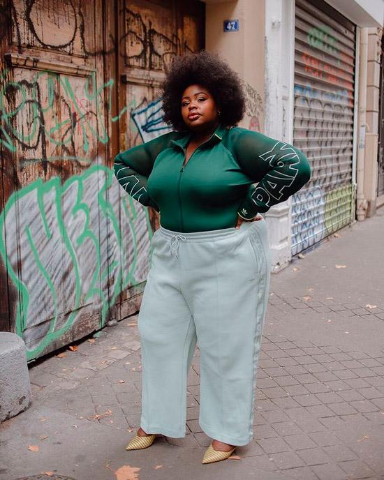 Девушка в светлых свободных брюках и зеленой олимпийке