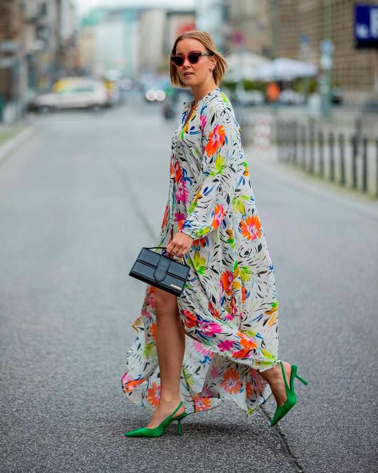 Девушка в свободном макси платье с ярким цветочным принтом, образ дополняют зеленые остроконечные туфли с открытой пяткой и сумочка